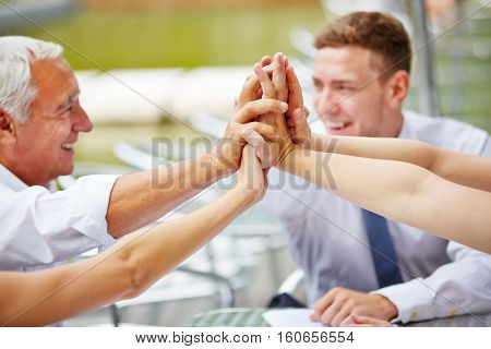 Many hands of business team giving high five for motivation