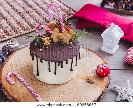 Homemade Christmas cake decorated with gingerbread men, waffles and candy canes on a rustic wood stand