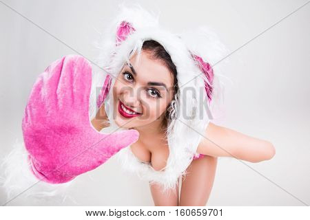 Portrait of handsome girl in rabbit costume that feel happy say hi putting her hand forward on light gray background