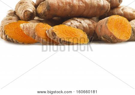 turmeric root and some slices on a white background
