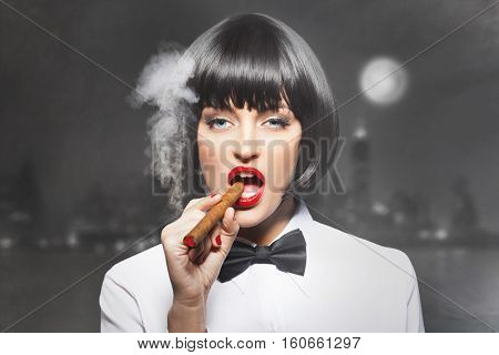 Sexy mafiosi woman boss smoke with cigar in town