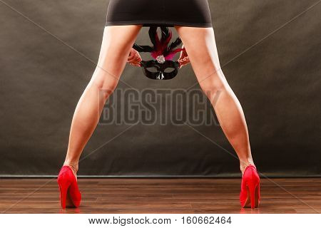 Holidays people and celebration concept. Woman legs in red high heels and carnival venetian mask on dark.