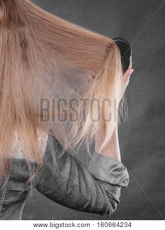 Blonde Woman Combing Her Hair.