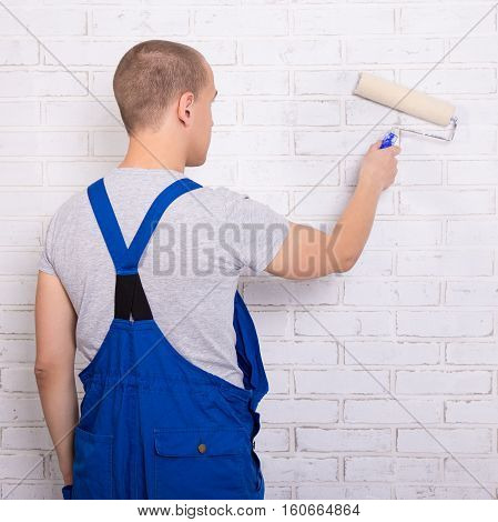 Rear View Of Man Painter In Workwear Painting Brick Wall With Paint Roller