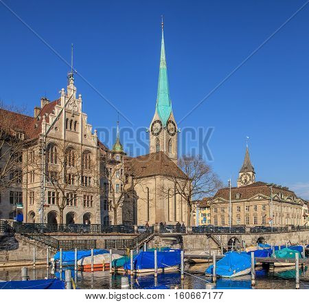 Zurich, Switzerland - 12 February, 2011: boats on the Limmat river, people on the embankment of the river, Zurich Town Hall, Fraumunster Cathedral and St. Peter Church in the background. Zurich is the largest city in Switzerland.