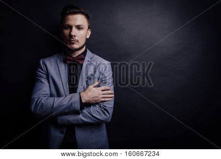 Portrait of handsome confident man in suit with butterfly looking forward on dark background