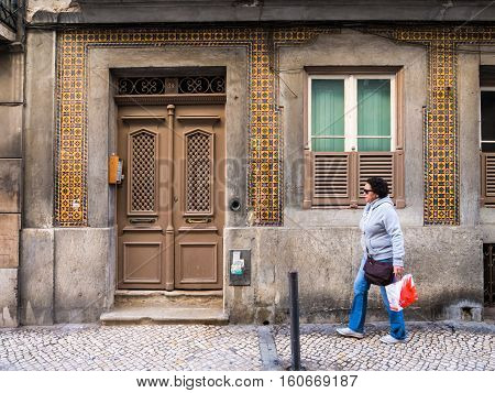 LISBON PORTUGAL - NOVEMBER 17 2016: Person passing next to an old building in Bairro Alto Lisbon Portugal.