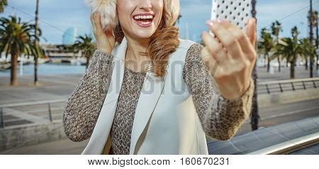 Woman On Embankment In Barcelona Taking Selfie With Smartphone