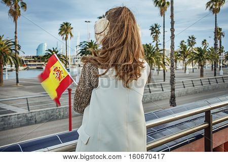 Modern Woman In Earmuffs In Barcelona With Spanish Flag