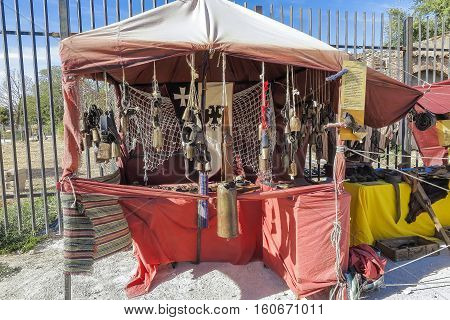 outdoor scene with a cowbells shop in the recreation of a medieval market. the market have free admission and is located on a public place