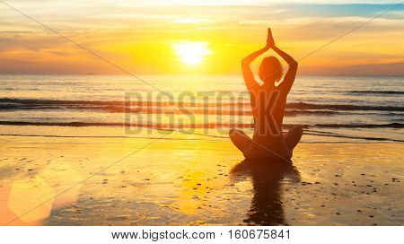Silhouette woman yoga on the sea beach at sunset.