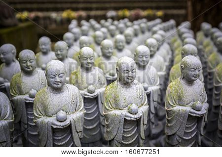 Rows of similar Japanese Jizo sculptures in Kamakura, Japan
