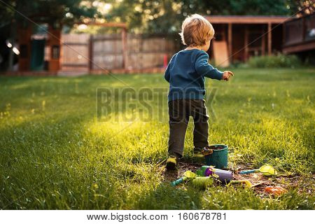 Boy on grass with pails . back view.