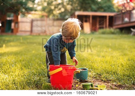 Young boy on playground with pail on grass