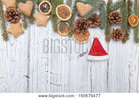 Christmas decoration frame on old grunge white wooden board with fur tree branches, cookies, pine cones., Top view with copy space.