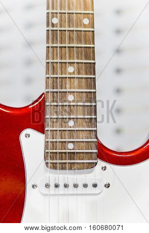 Close view of red electric guitar part with pickup