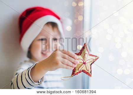 A boy holding a Christmas toy star Glitter gold and red tinsel. Joyful Christmas story red hat of Santa Claus