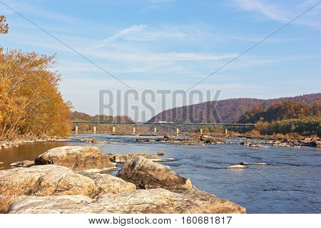 A bridge across Potomac River near Harpers Ferry West Virginia USA. Autumn landscape of Blue Ridge Mountains and Potomac River.