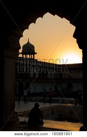 AGRA INDIA - Nov 27 2016: Unidentified tourism walk abround in Unesco World Heritage silhouette of the walls famous red fort tower dome Agra Fort in Uttar Predesh India on 27 November 2016.