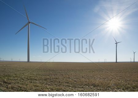 Close up of a wind turbine in the foreground and multiple windmills in a large wind farm in the background. The image is backlit with sun rays extending from the upper right corner creating a bokeh effect.