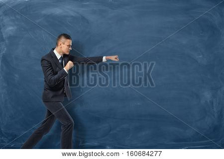 A businessman in a black suit standing as if he is going to punch something invisible near the blue chalkboard. Aggressive marketing strategies. Business development. Successful leader.