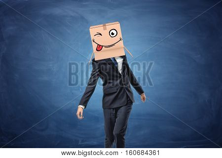 Businessman wearing cardboard box with drawn winking face on his head on blue chalkboard background. Time to have fun. Crazy idea. Attracting clients.