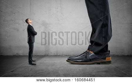 Tiny businessman looking up on huge legs of another businessman. Career growth and opportunities. Confident behaviour.