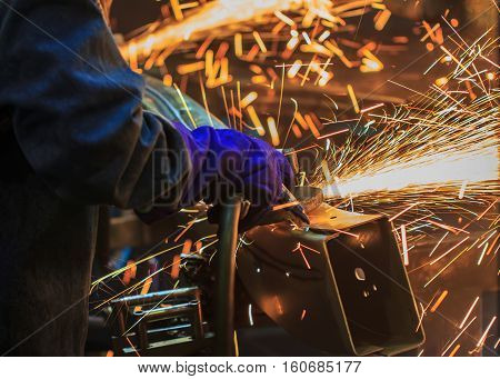 Flame sparks with electric grinder the swaying back and forth all the time