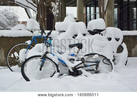 Snow Covered Bicycles in a Blizzard on a Cold Winter Day