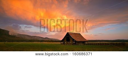 A barn with a vivid sunset clouds hovering above in Northern California.
