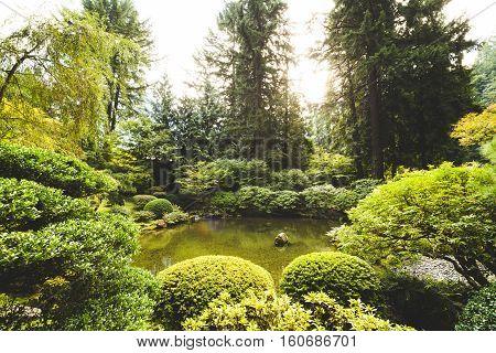 Metal animal sculptures in a beautiful, green garden landscape. Portland Japanese Garden, Portland, Oregon, USA.