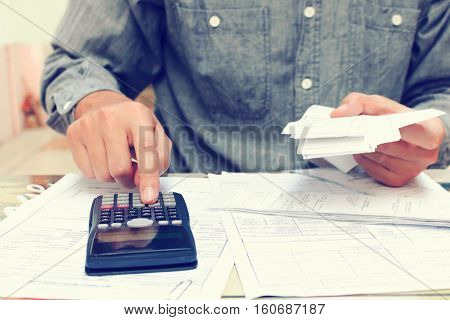 Young asian man using calculator and calculating bills in home office.