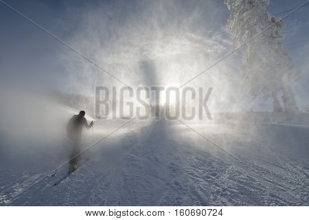 snowstorm in the mountains. skier going to the top of the mountains