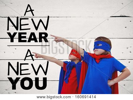 Children in super hero costumes pointing at new year greeting quotes against wooden background