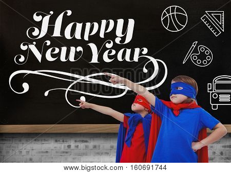 Children in super hero costumes pointing at new year greeting quotes on blackboard