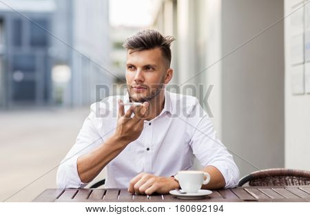 business, technology, communication and people concept - young man with coffee using voice command recorder on smartphone at city street cafe