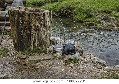Washing dishes. Camping cooking gear. Dirty plates and dishes on a campsite waiting to be washed up.Apuseni Mountains in Romania. Natural background.