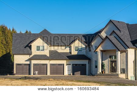 Giant new residential house with four stall garage and unpaved driveway in front