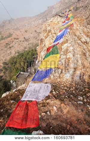 Lungta (horse of wind) - the Tibetan prayful flags over a mountain ridge with Mahakala's cave the place where the prince and then the ascetic Siddhartha Gautama have spent some time in an ascesis.