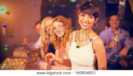 Portrait of friends having tequila in bar against flying colours