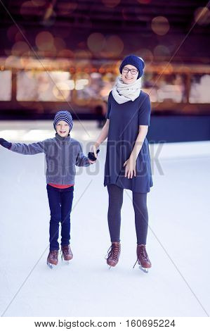 beautiful family of two enjoying winter holidays and ice skating at outdoor rink winter vacation activity