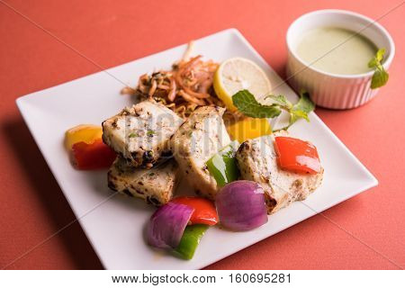 Paneer Tikka Kabab - Tandoori Indian cheese skewers or chilli paneer served in white plate  with green sauce and colourful salad, selective focus