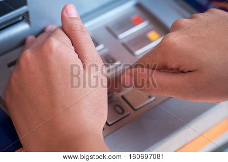 Close-up of hand entering PIN/pass code on ATM/bank machine keypad. Selective focus on hand.