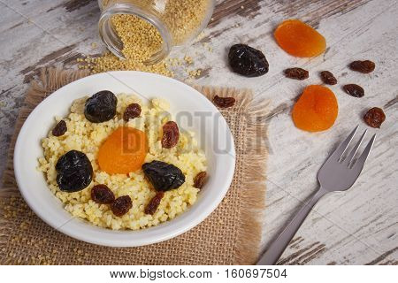 Fresh cooked millet groats with raisins dried apricot and plum on white plate concept of healthy food nutrition and nutritious breakfast