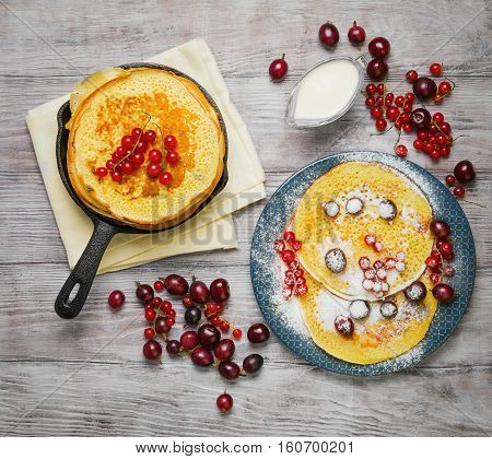 Pancakes fritters in cast iron skillet stack hash browns pancakes on plate with berries. Berries for pancakes crepes red currants gooseberries cherries sour cream. Light white wooden background. Top view.