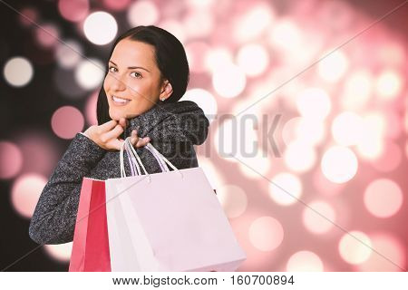 Smiling woman holding shopping bag against light circles on black background