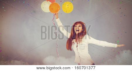 Smiling hipster woman holding balloons against illuminated disco lights at disco