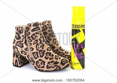 SWINDON UK - DECEMBER 4 2016: Pair of Leopard Skin Boots with a can of Loreal Studio Pro Lock It hair spray