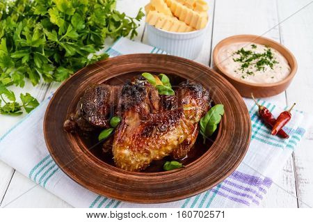 Fried wings (duck chicken) in a honey glaze in a clay bowl on a light background.