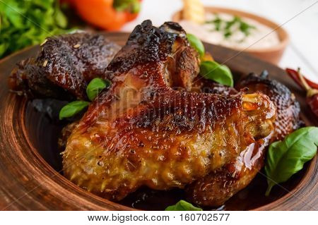 Fried wings (duck chicken) in a honey glaze in a clay bowl on a light background. Close up